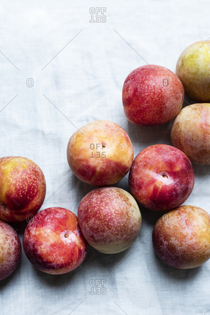 Red plums on linen tablecloth