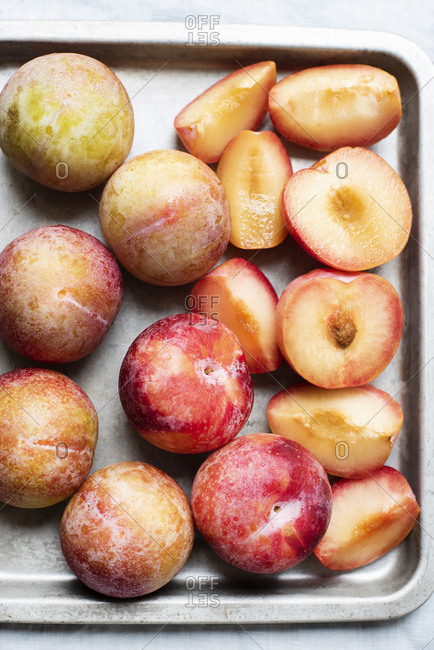 Whole and sliced plums on a tray