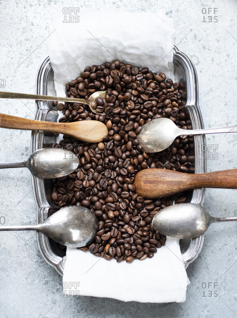Coffe beans in vintage bowl with different spoons