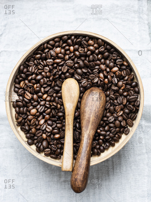 Coffee beans in wood bowl and wooden spoons