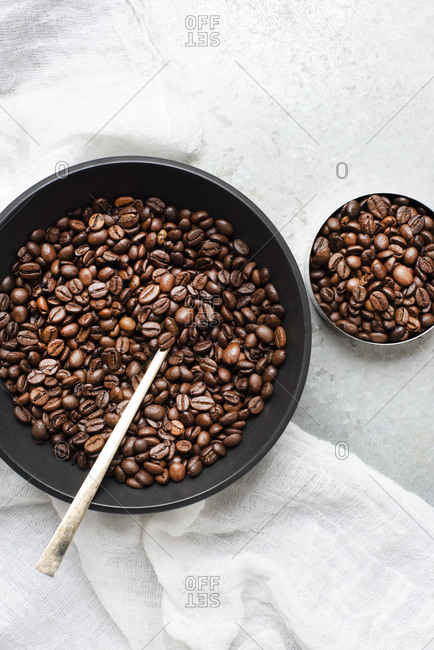 Coffee beans in bowls with gold spoon