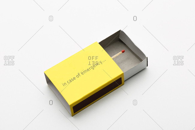 Yellow matchbox with a match inside, on white background.