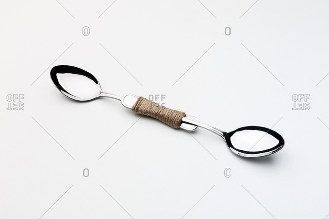 "Two spoons tied together by a rope on white background. ""Solidarity""."