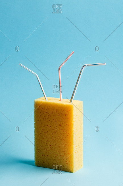 Yellow sponge with three drinking straws. On blue background.