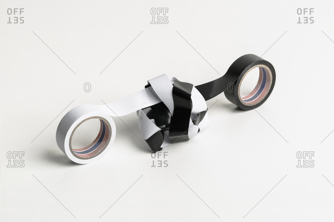 Two rolls of adhesive tape (black and white) are intertwined on white background.