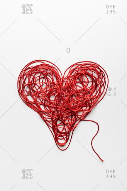 Messy heart made with red thread, on white background.