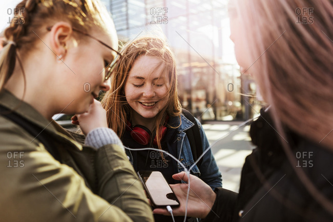 Teenage girl looking at friends listening music through mobile phone in city