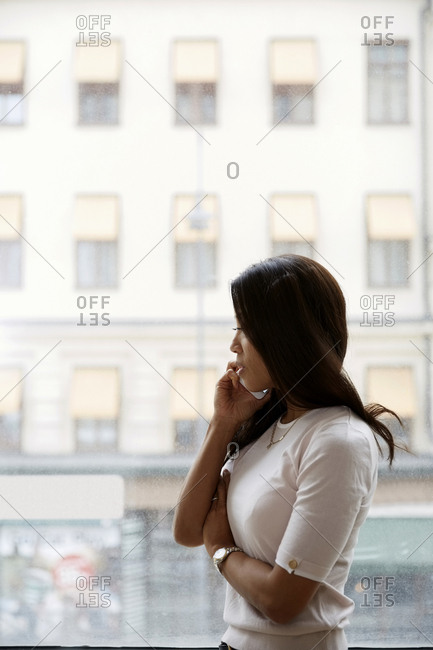 Side view of businesswoman talking on mobile phone while standing by window at office
