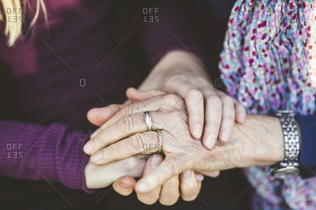 Cropped image of granddaughter and grandmother holding hands
