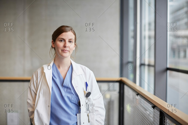 Portrait of confident mid adult female doctor by window in corridor at hospital