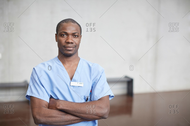 Portrait of confident mid adult male nurse standing with arms crossed in corridor at hospital