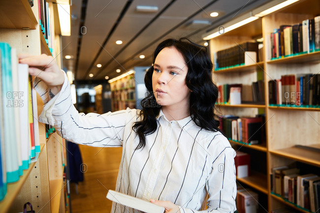 Young female student searching book in university library