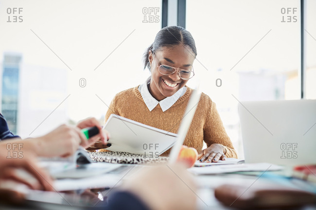 Smiling woman studying while sitting with friends at table in university cafeteria