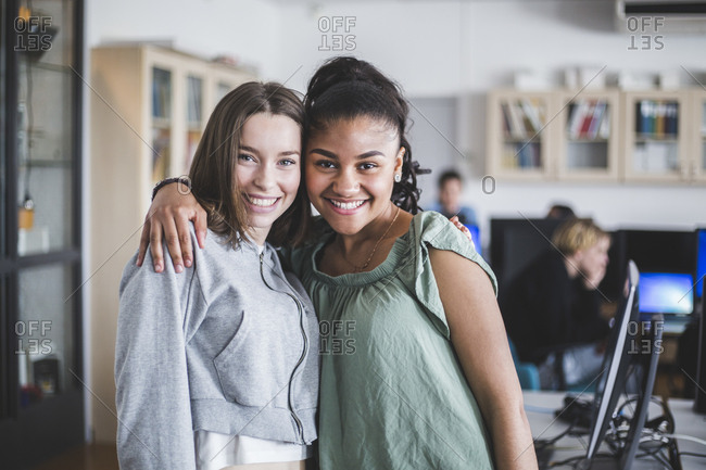 Portrait of smiling female teenage friends standing with arm around in computer lab at high school