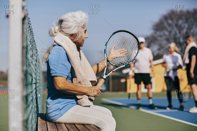 Senior woman holding tennis racket while sitting on bench at tennis court