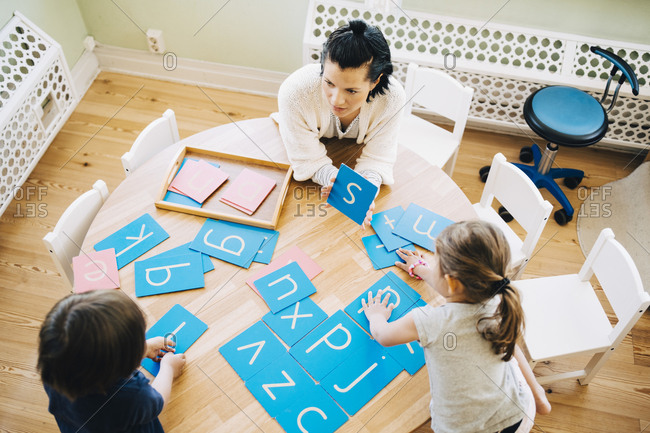 High angle view of confident female teacher showing letter S to students at table in classroom
