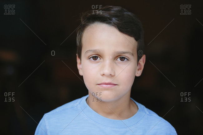 Close-up portrait of serious boy standing in darkroom at home