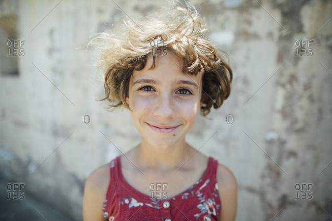 Close-up portrait of smiling girl with short hair standing against wall
