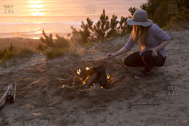 Woman crouching by campfire at beach during sunset