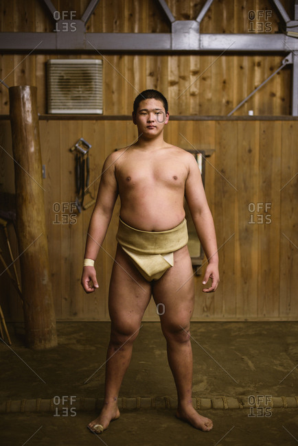 Japan, Niigata - October 26, 2017: Portrait of confident shirtless wrestler standing against wooden wall in sumo beya