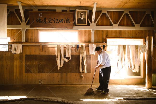 Japan, Niigata - October 26, 2017: Side view of man sweeping in sumo beya