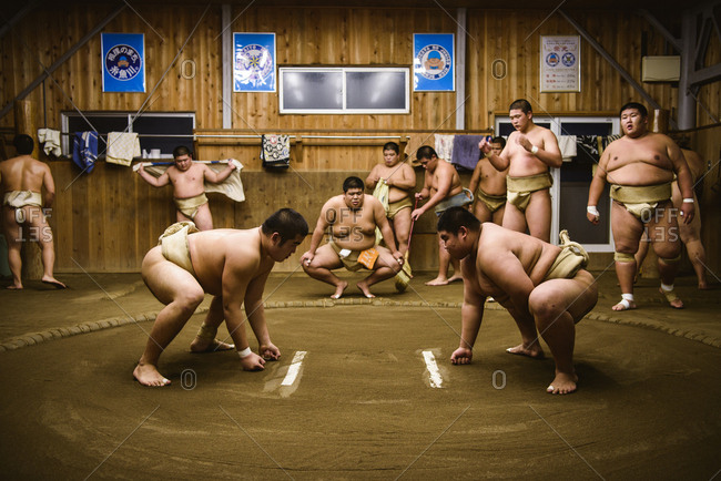Japan, Niigata - October 25, 2017: Men looking at sumo wrestlers wrestling in beya