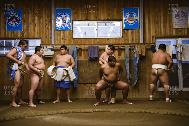 Japan, Niigata - October 25, 2017: Wrestlers getting dressed while standing against wooden wall in sumo beya