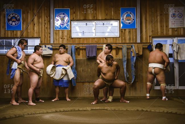 Japan, Niigata - October 25, 2017: Wrestlers getting dressed while standing against wooden wall in sumo beya