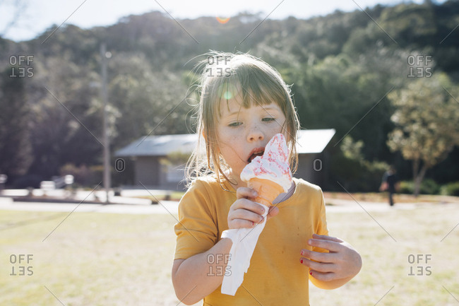Cute girl eating ice cream cone while standing against trees at park during sunny day