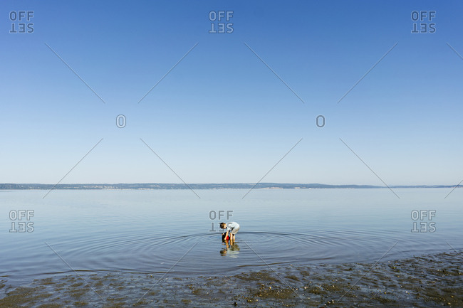Side view of boy filling bucket while standing in sea against clear blue sky during sunny day