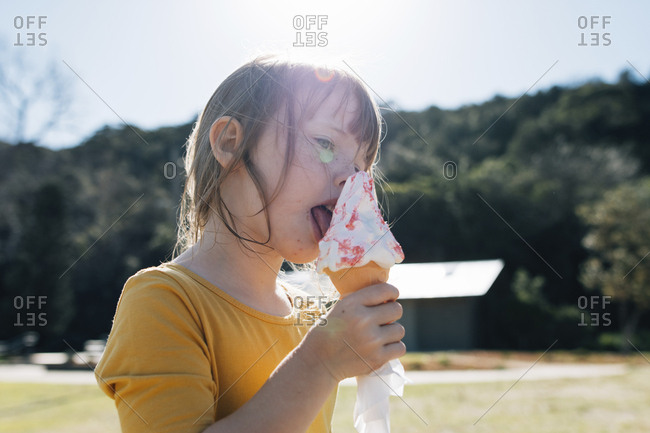Cute girl eating ice cream cone while standing against sky at park during sunny day