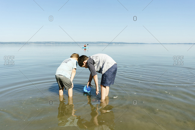 Brothers playing with water while standing in sea against clear blue sky during sunny day