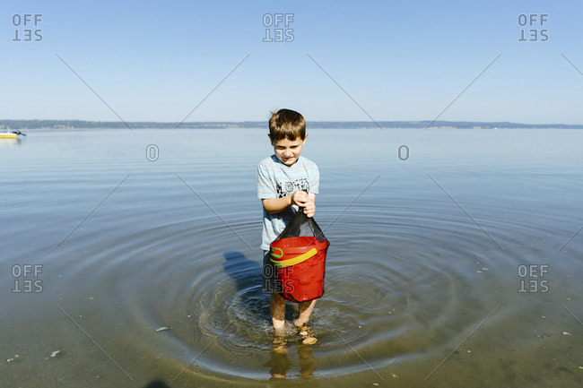 Boy carrying bucket while standing in sea against clear blue sky during sunny day
