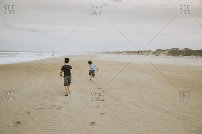 Rear view of brothers walking on sand at beach against cloudy sky