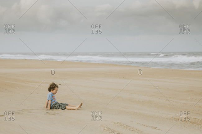 Side view of boy sitting on sand at beach against cloudy sky