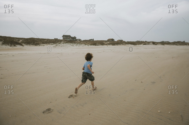 Rear view of boy running on sand at beach against cloudy sky