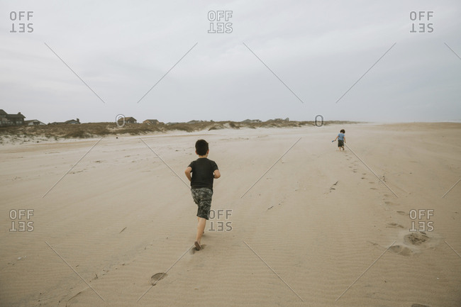Rear view of boy running towards brother at beach against cloudy sky