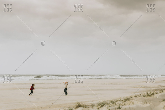 Brothers playing at beach against cloudy sky