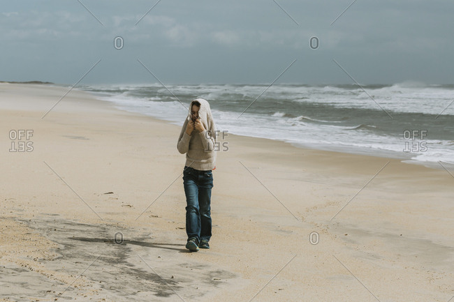 Boy covering head with sweater while walking at beach against sky during sunny day