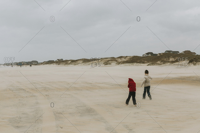 Rear view of brothers running at beach against cloudy sky