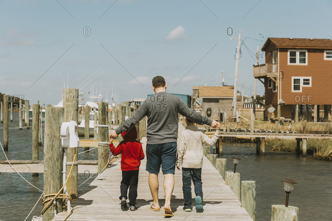 Rear view of father with sons walking on pier over sea against sky during sunny day