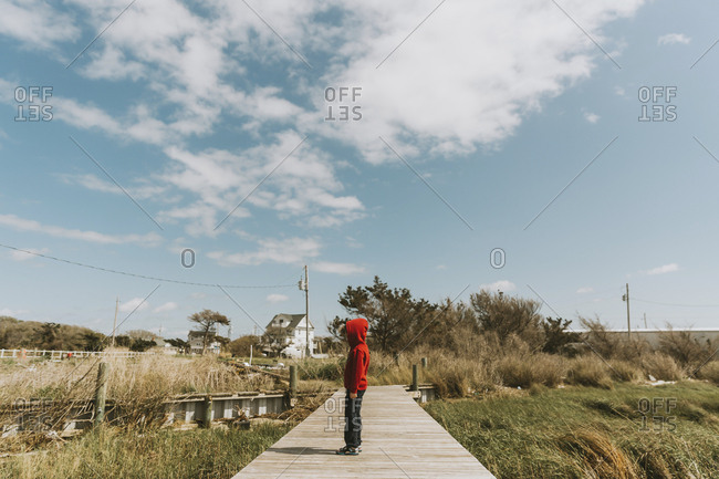 Side view of boy in hooded jacket standing on boardwalk amidst plants against sky during sunny day