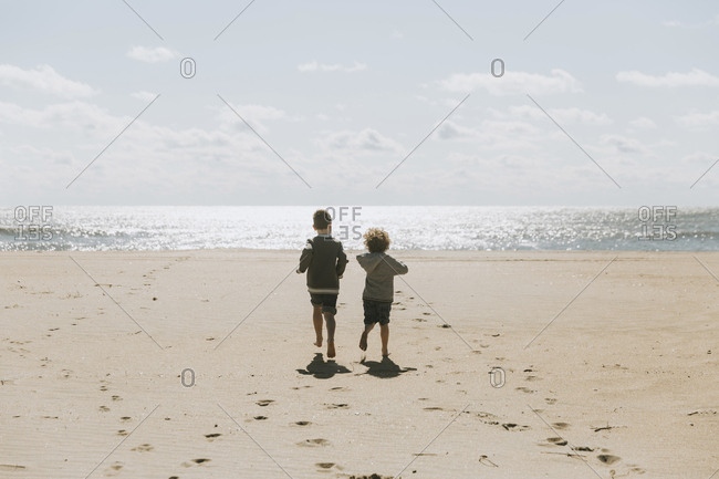 Rear view of brothers running towards sea at beach against sky during sunny day