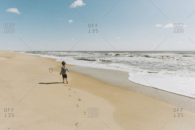 Rear view of boy walking at beach against sky during sunny day