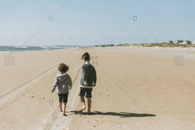 Rear view of brothers walking on sand at beach against sky during sunny day