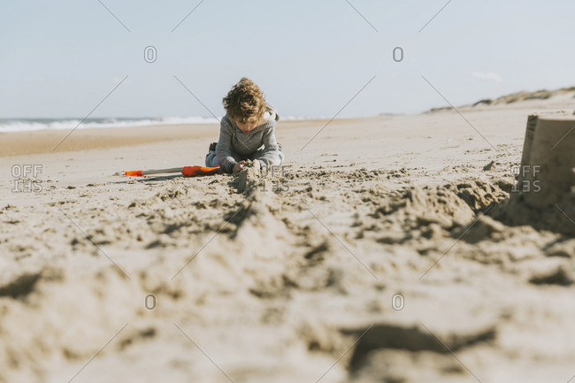 Boy making sandcastle at beach against clear sky during sunny day