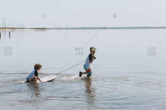 Side view of boy pulling brother sitting on surfboard in sea against clear sky during sunny day