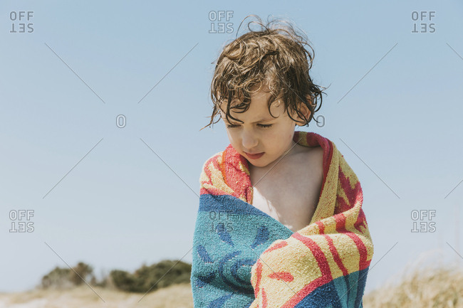 Low angle view of shirtless wet boy with towel standing against clear sky at beach during sunny day
