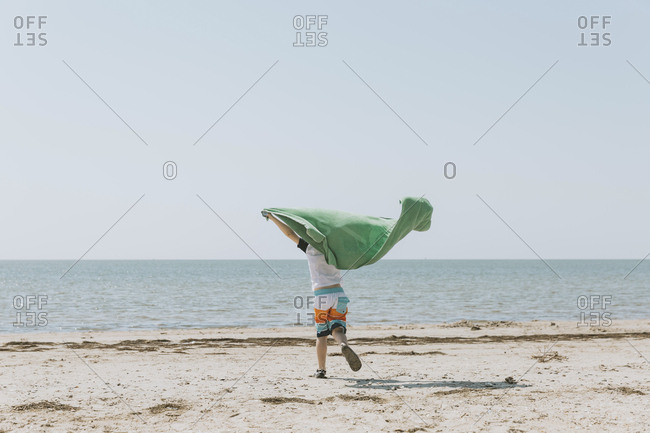 Rear view of boy with green towel running at beach against clear sky during sunny day