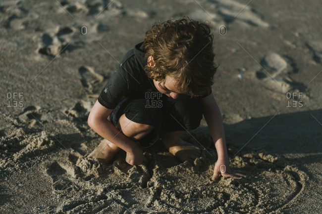 High angle view of boy playing with sand while crouching at beach during sunny day